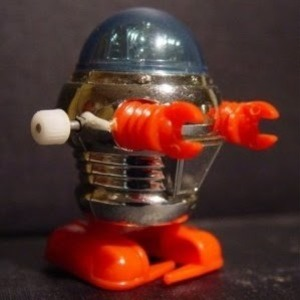 image of silver, blue, and orange windup robot toy from the 1970s